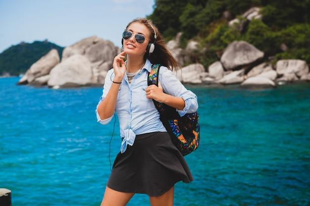Schöne hipster-frau, die mit rucksack um die welt reist, lächelnd, glücklich, positiv, musik in kopfhörern hörend, blauer tropischer ozeanhintergrund, sonnenbrille, sexy, sommerferien,