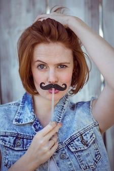 Schöne hipster frau hält einen falschen schnurrbart an ihr gesicht,
