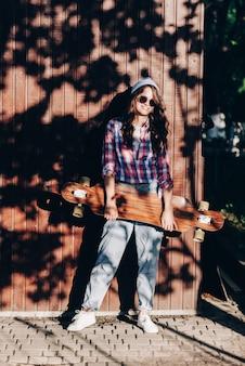 Schöne hipster mode junge frau modell posiert mit skateboard auf stadt hintergrund in mode sonnenbrillen Premium Fotos