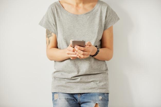 Schöne hipsterfrau, die e-mail über handy während graue wand prüft