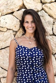 Schöne hispanische frau im blauen kleid, das auf wand beim schauen der kamera sich lehnt