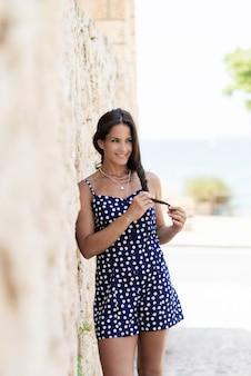 Schöne hispanische frau im blauen kleid, das auf wand beim weg schauen sich lehnt