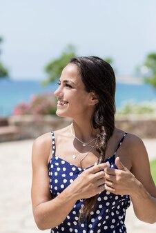Schöne hispanische frau im blauen kleid, das gegen meer beim berühren des haares steht