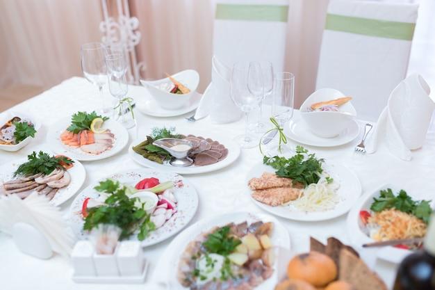Schöne hochzeitsblumendekoration auf einem tisch mit catering-essen in einem hellen restaurantsaal mit weißen tischdecken