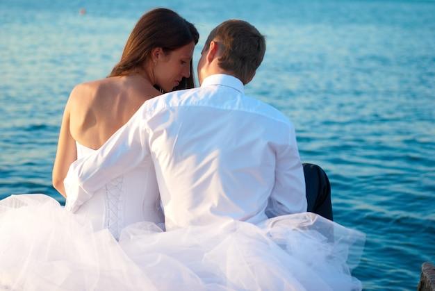 Schöne hochzeitspaar braut und bräutigam, die am strand umarmen