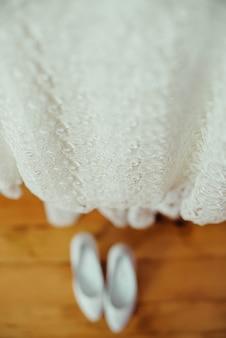 Schöne hochzeitsschuhe und -kleid auf einem hölzernen braunen boden