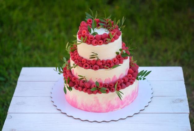 Schöne hochzeitstorte in drei ebenen mit weißer und rosa creme, dekoriert mit frischen himbeeren, im sommergarten