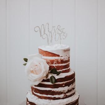 Schöne hochzeitstorte verziert mit weißen rosen auf weißem hölzernem hintergrund