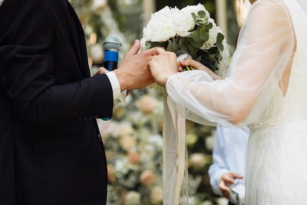 Schöne hochzeitszeremonie. hochzeitsbogen vom bräutigam mit nesty. glückliches brautpaar bei der zeremonie. besuchszeremonie. ein schönes paar.