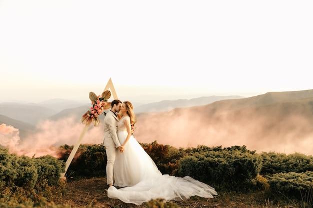 Schöne hochzeitszeremonie in den bergen, hochzeitspaar von jungvermählten in liebesumarmung.