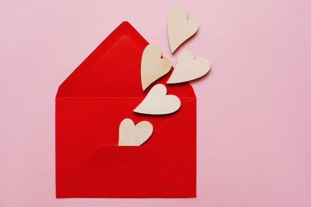 Schöne hölzerne herzen auf einer roten papierumschlag-liebesnachricht