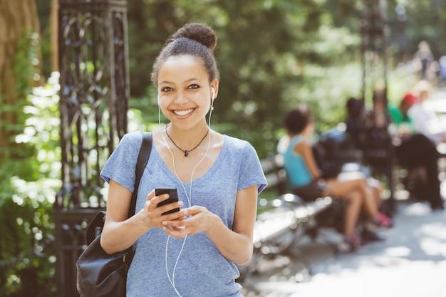 Schöne hörende musik der mischrasse-jungen frau mit kopfhörern am park