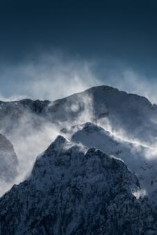Schöne hohe schneebedeckte und neblige berge mit schnee, der vom wind geblasen wird