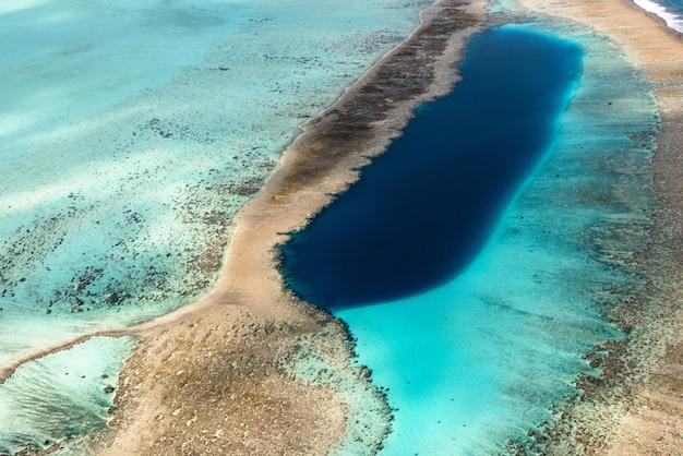 Schöne hohe winkelaufnahme einer wilden naturszene des ozeans gemischt mit dem sand