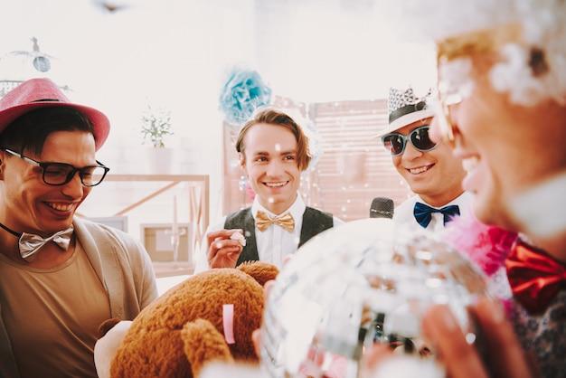 Schöne homosexuelle kerle, die an einer homosexuellen party lächeln.