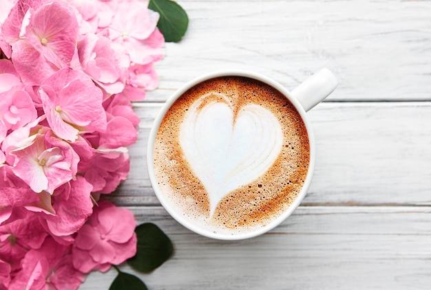 Schöne hortensienblumen und kaffeetasse auf rustikalem weißem holz, flach gelegen.