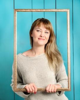 Schöne hübsche blonde junge frau im gestrickten pullover mit losen haaren hält vintage hölzernen bilderrahmen und lächelt
