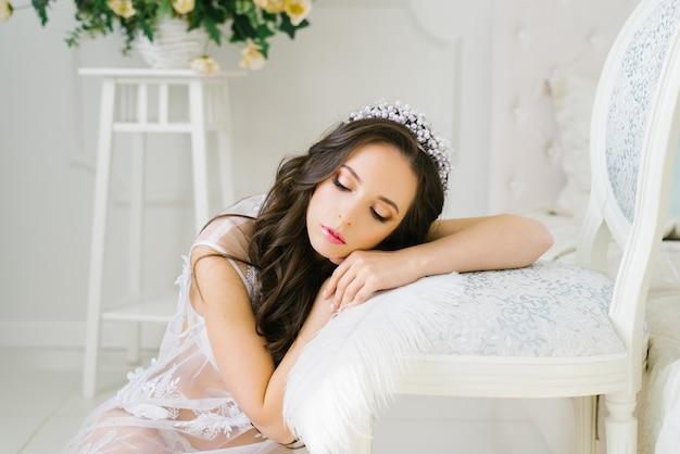 Schöne hübsche brünette braut lehnte sich auf einen stuhl und legte sich darauf, schloss die augen, ruhiger schlaf.