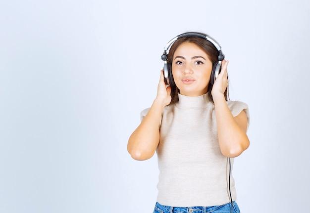 Schöne hübsche frau, die in die kamera schaut und die musik über kopfhörer hört.