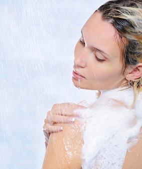 Schöne hübsche frau, die unter wasserströmen steht - nahaufnahme