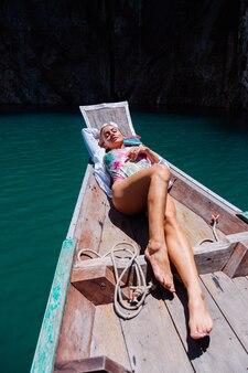 Schöne hübsche frau im badeanzug am rand auf boot