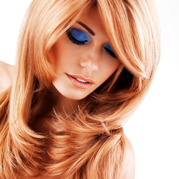 Schöne hübsche frau mit langen roten haaren. porträt des jungen modemodells mit blauem augenmake-up lokalisiert auf weißer wand