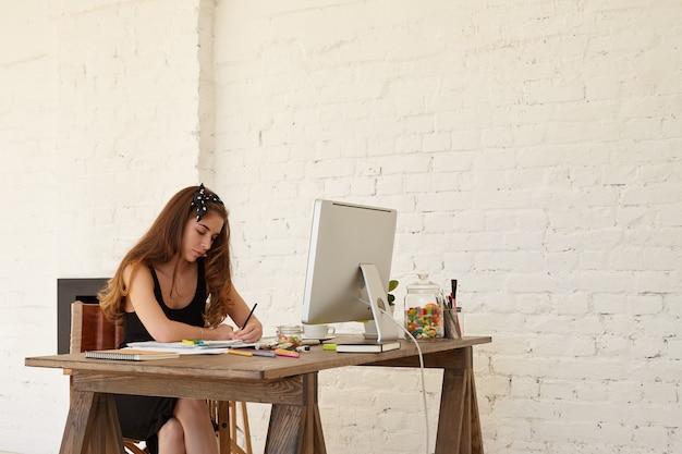Schöne hübsche junge frau, die schwarzes bürokleid und bw kopftuch trägt, sitzt am schreibtisch mit pc-computer, während sie werbung für privaten kindergarten schafft. kreativität, kunst, business, arbeitskonzept