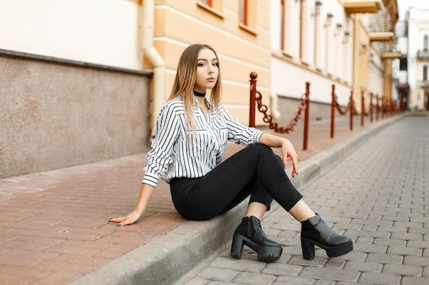 Schöne hübsche junge frau in einer eleganten schwarz-weiß gestreiften bluse in trendigen jeans in lederschuhen mit einer durchbohrten nase, die draußen in der stadt sitzt.