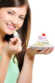Schöne hübsche junge frau mit dem kuchen auf teller auf weiß