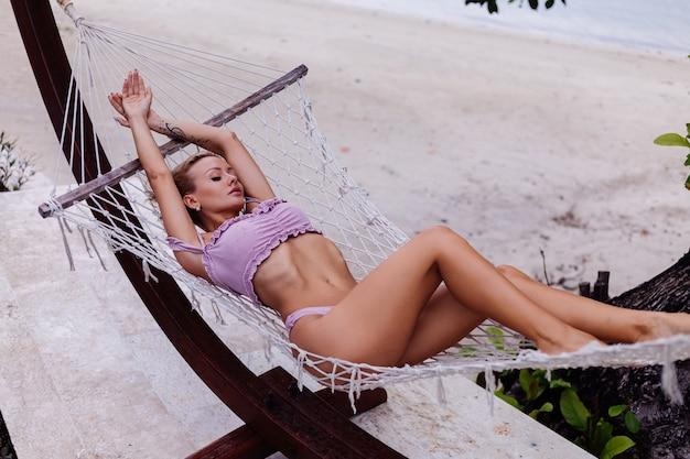 Schöne hübsche kaukasische blonde gebräunte frau im lila bikini liegt auf hängematte