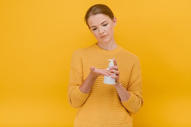 Schöne hübsche lässig gekleidete frau verwendet ein antiseptisches desinfektionsmittel oder flüssigseife auf ihrem handreinigungskonzept