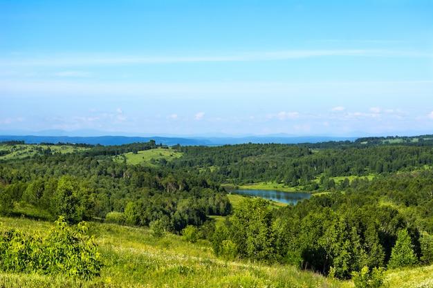 Schöne hügellandschaft des sommers mit blauem see