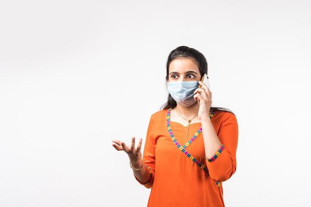 Schöne indische frau, die mit ihrem handy spricht, während sie eine medizinische schutzmaske trägt und isoliert über der weißen wand steht