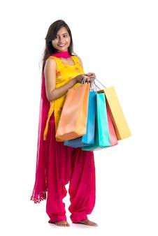 Schöne indische junge frau, die mit einkaufstaschen hält und aufwirft