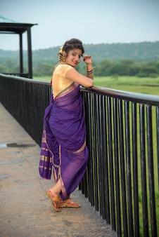 Schöne indische junge frau im traditionellen saree, der draußen aufwirft