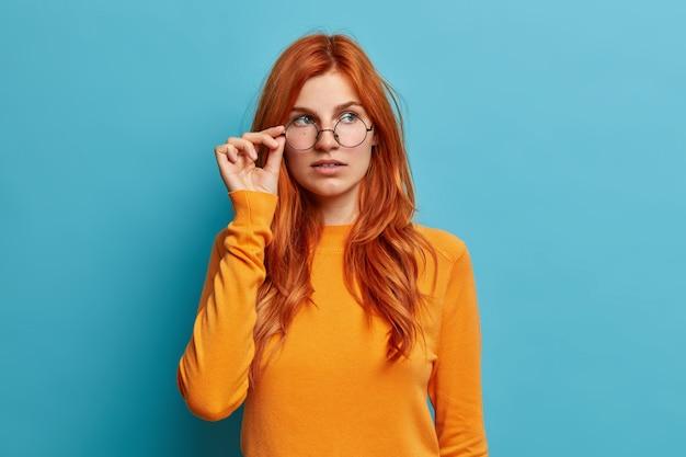 Schöne ingwer studentin denkt über zukünftige projekt hält hand auf brille konzentriert nachdenklich beiseite gekleidet in lässigen orange pullover konzentriert.