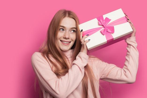 Schöne ingwerfrau mit sommersprossen und roten haaren schüttelt ein geschenk und lächelt auf einer rosa studiowand