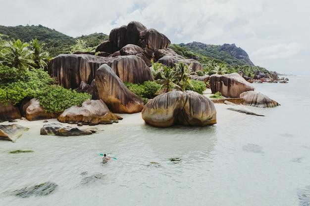 Schöne insel auf den seychellen. la digue, anse d'argent strand mit luftaufnahme. mann kajak mit transparentem kajak am morgen