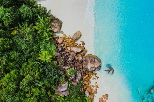 Schöne insel auf den seychellen. la digue, anse d'argent strand. wasser fließt und wellen schäumen auf einer tropischen landschaft