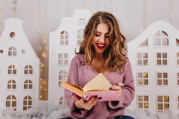 Schöne intelligente brünette mit hellem lippenstiftlesespaßbuch in gemütlicher weihnachtsatmosphäre. porträt des mädchens mit dem lockigen haar