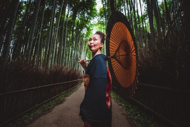 Schöne japanische ältere frau, die im bambuswald geht