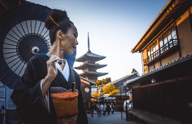 Schöne japanische ältere frau, die im dorf geht. typischer traditioneller japanischer lebensstil