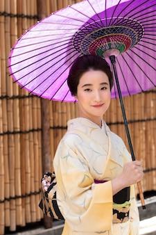 Schöne japanische frau mit einem lila regenschirm