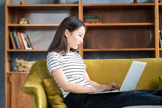 Schöne japanische freiberuflerin, die am computer im hotel auf der couch lächelt und tippt