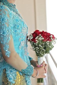 Schöne javanische frauen, die den batik anhält rotrose tragen