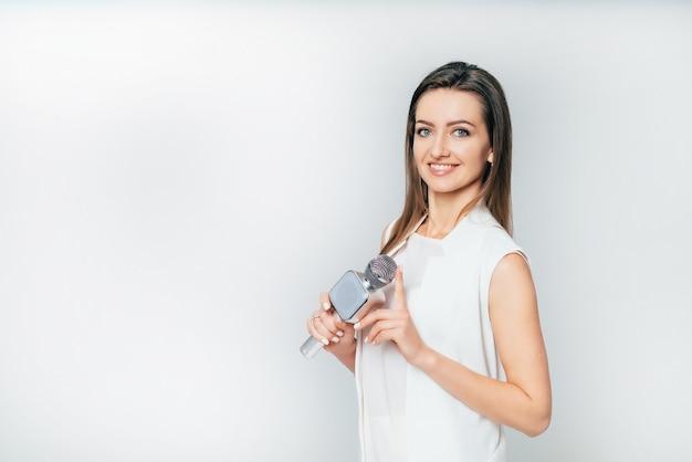 Schöne journalistin lächelt und hält in der hand ein mikrofon