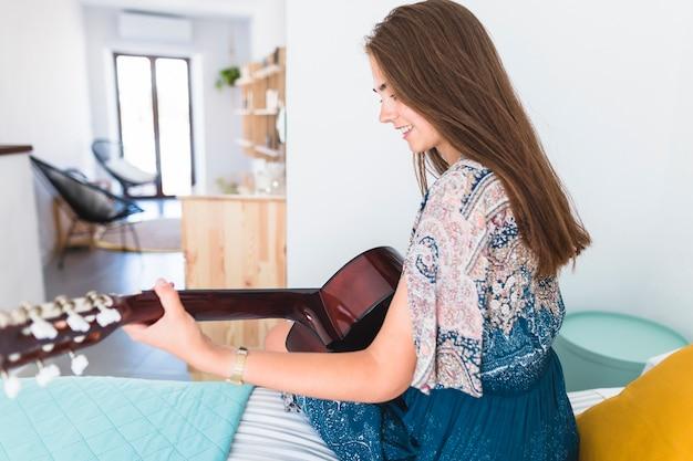 Schöne jugendliche, die auf dem bett spielt gitarre sitzt