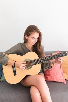 Schöne jugendliche, die auf dem sofa spielt gitarre sitzt
