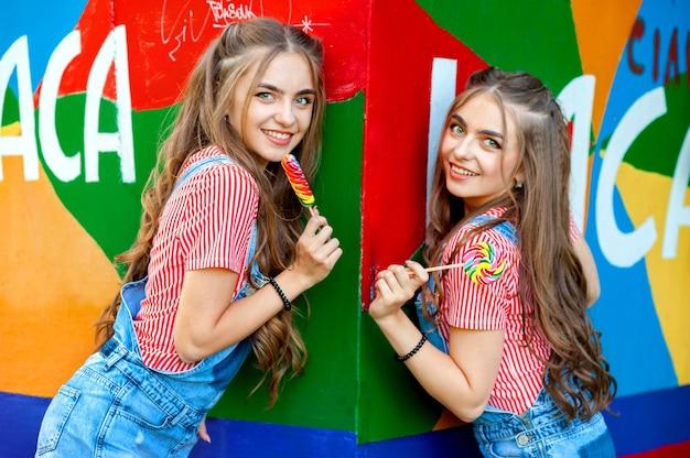 Schöne jugendliche zwillingsschwestern in den bunten kleidern mit lutschern an der bunten wand