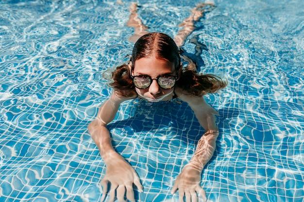 Schöne jugendlichmädchenschwimmen am pool mit moderner sonnenbrille. spaß im freien. sommer und lifestyle-konzept